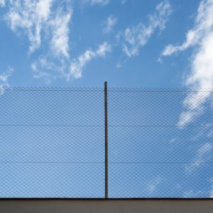 Metal Rabitz mesh fence against blue sky